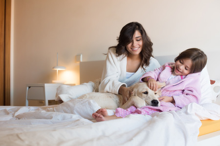 Mother and daughter with dog in bed Stock Photo
