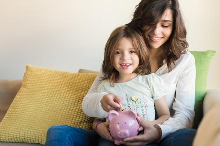 母と娘の貯金箱にコインを入れ 写真素材