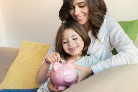 Mutter und Tochter, die Münzen in Sparschwein Standard-Bild - 48470870