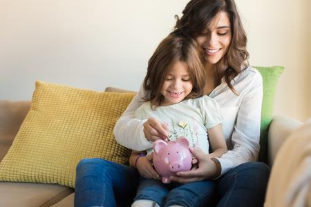 돼지 저금통에 동전을 넣어 어머니와 딸