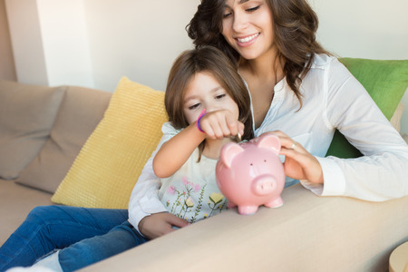 family sofa: Mother and daughter putting coins into piggy bank