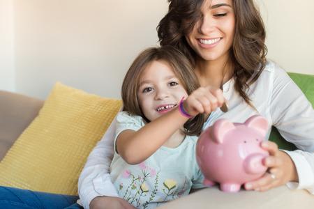 Mutter und Tochter, die Münzen in Sparschwein Standard-Bild - 48470884