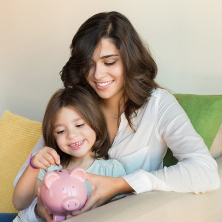 livingroom: Mother and daughter putting coins into piggy bank