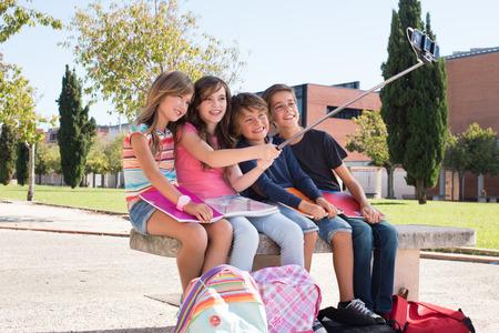 escuela primaria: Niños de la escuela de tomar imágenes con el palillo selfie