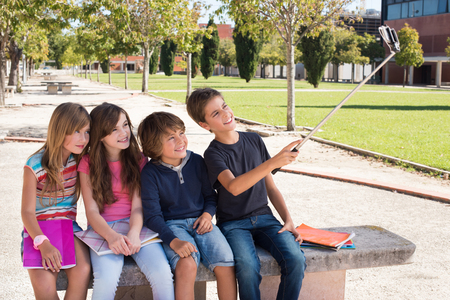 young group: School kids talking photos with a selfie stick