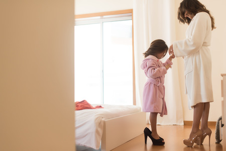 girl shoes: Little girl wearing heels with her mother in bedroom Stock Photo