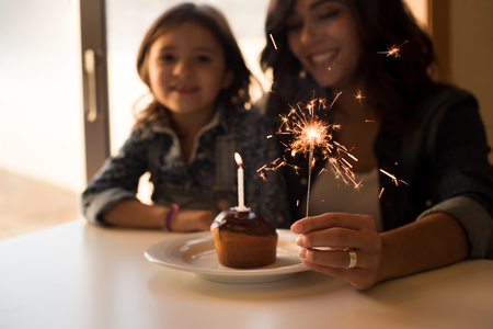 children birthday: Mother and daughter celebrating birthday with cupcake and sparklers Stock Photo
