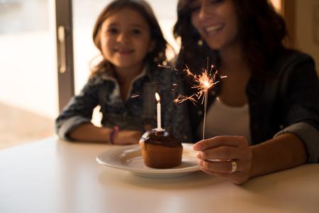 mama e hija: Madre e hija celebrando el cumpleaños con la magdalena y bengalas