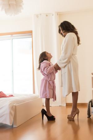 Little girl wearing heels with her mother in bedroom Standard-Bild