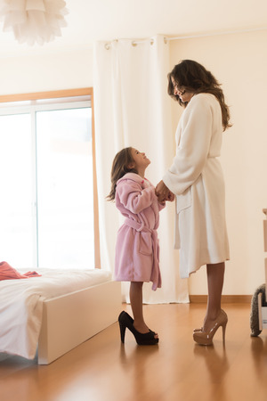 heel: Little girl wearing heels with her mother in bedroom Stock Photo