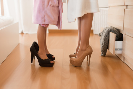 Little girl wearing heels with her mother in bedroom Foto de archivo