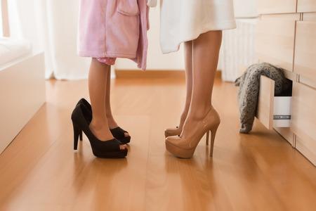 Little girl wearing heels with her mother in bedroom Archivio Fotografico