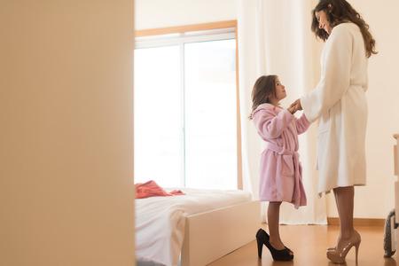 madre e hija: La niña que desgasta los talones con su madre en el dormitorio Foto de archivo