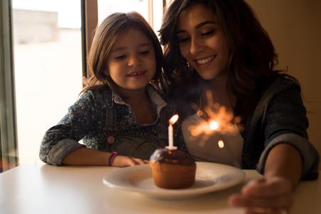 torta compleanno: Madre e figlia festeggiare il compleanno con il bigné e stelle filanti Archivio Fotografico