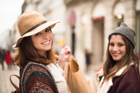 consumerism: Trendy young women shopping in the city