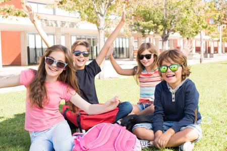 niños felices: Pequeño grupo de estudiantes que se sientan en la hierba en la escuela Foto de archivo