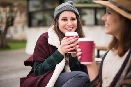 Couple of friends with hot drink on winter Foto de archivo