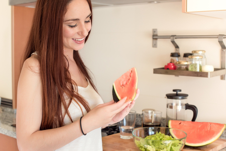 red hair girl: Young woman eating watermelon in the kitchen