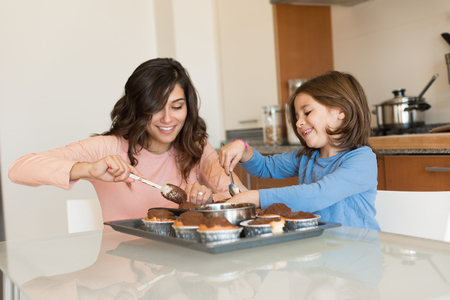 Mother and daughter making cupcakes in kitchen