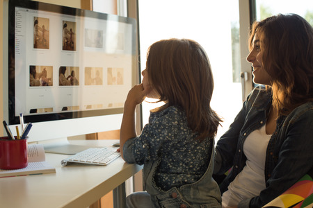 Mother and daughter watching their photos on computer
