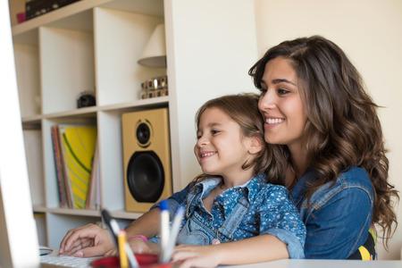 Mujer joven con la niña que usa el ordenador en el hogar