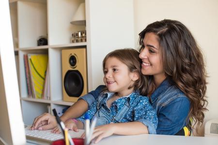 집에서 컴퓨터를 사용하는 어린 소녀와 젊은 여자 스톡 콘텐츠
