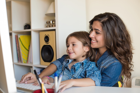 Young woman with little girl using computer at home Banque d'images