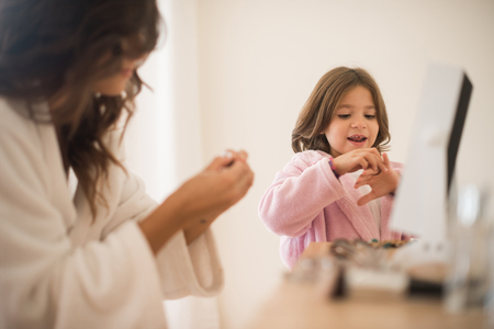 bead jewelry: Little girl playing with her mother jewellery and make up