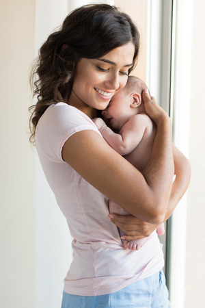 pretty baby: Pretty woman holding a newborn baby in her arms