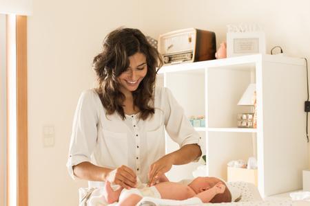 diaper changing table: Mother changing a diaper on newborn baby