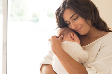 lactancia materna: Mujer bonita que sostiene un bebé recién nacido en sus brazos