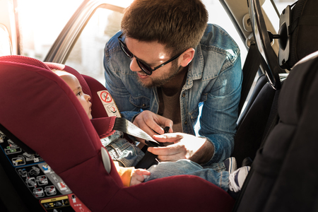 父が車の座席に彼の小さな赤ちゃんを固定します。