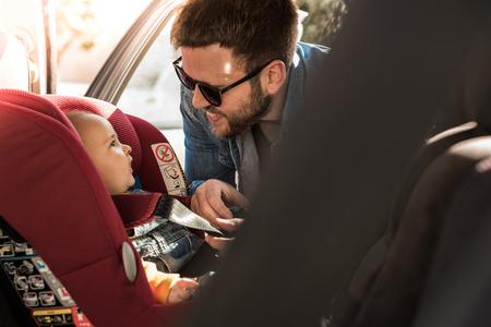 父が車の座席に彼の小さな赤ちゃんを固定します。 写真素材