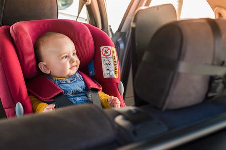 아버지는 차 좌석에 자신의 작은 아기를 고정