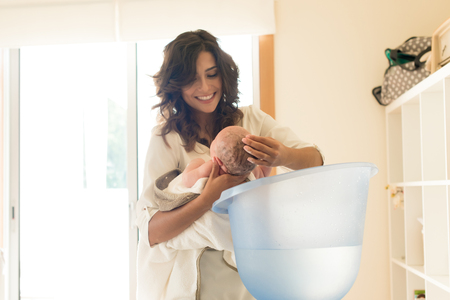 Mother washing a newborn baby in a bath tub