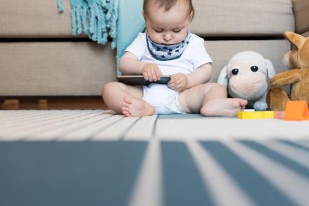 Pequeño bebé que juega con un smartphone - Adicción a la tecnología Foto de archivo - 82856536