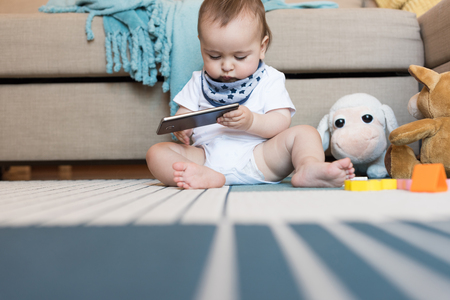 Little baby playing with a smartphone - Technology addiction