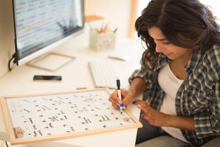 Woman on computer desk writing on calendar Stock fotó