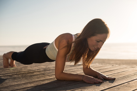 Women having a time doing pilates on the beach Banco de Imagens