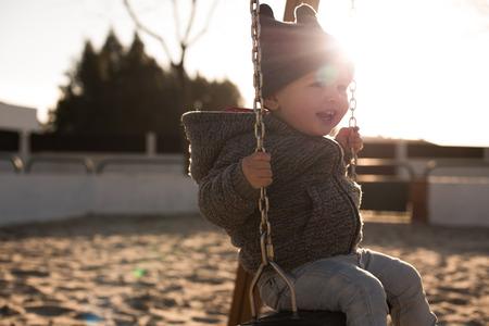 Toddler having fun on a swing seat - Sunset Light Foto de archivo - 100831916