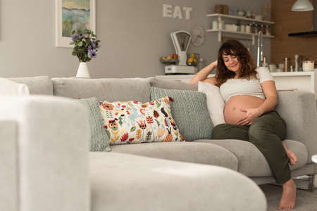 Happy pregnant woman sitting and touching her belly at home