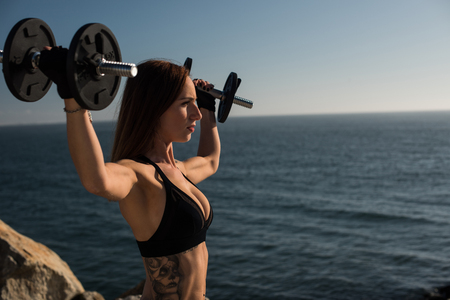Fitness woman with tattoos lifting weights - Outdoor Stock Photo