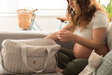 Young mother organizing the baby maternity bag
