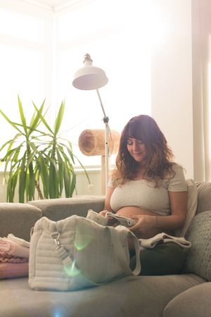 Pregnant woman packing maternity bag for hospital labor Stock Photo