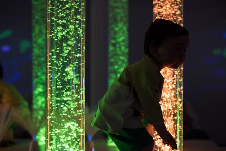 Young kid exploring a multi sensory space - snoezelen concept Stock Photo