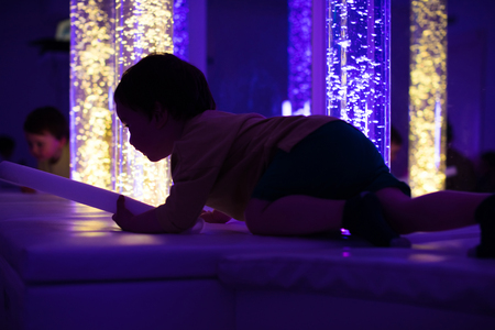 Young kid exploring a multi sensory space - snoezelen concept Stock Photo