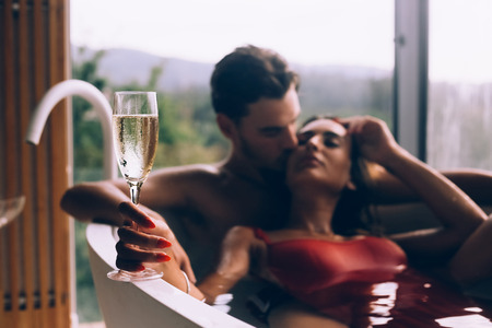 Beautiful couple enjoying a relaxing bath with champagne Banco de Imagens