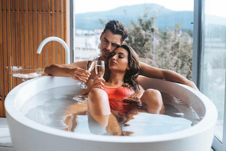 Schönes Paar, das ein entspannendes Bad mit Champagner genießt