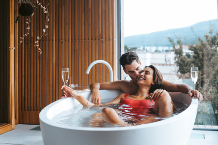 Beautiful couple enjoying a relaxing bath with champagne Фото со стока - 108466936