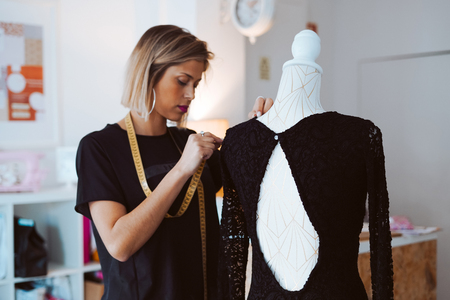 Tailor woman working on new dress at the atelier Stock Photo